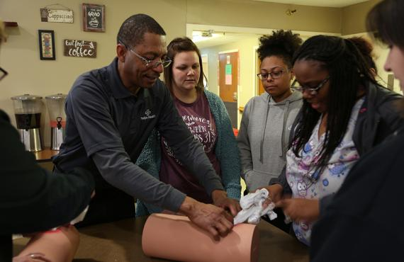 Instructor teaching students to control bleeding