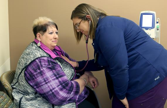 Nurse checking blood pressure of patient