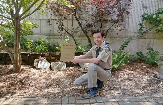 Scout WIl Baur holding a plaque in front of Bond Memorial Garden